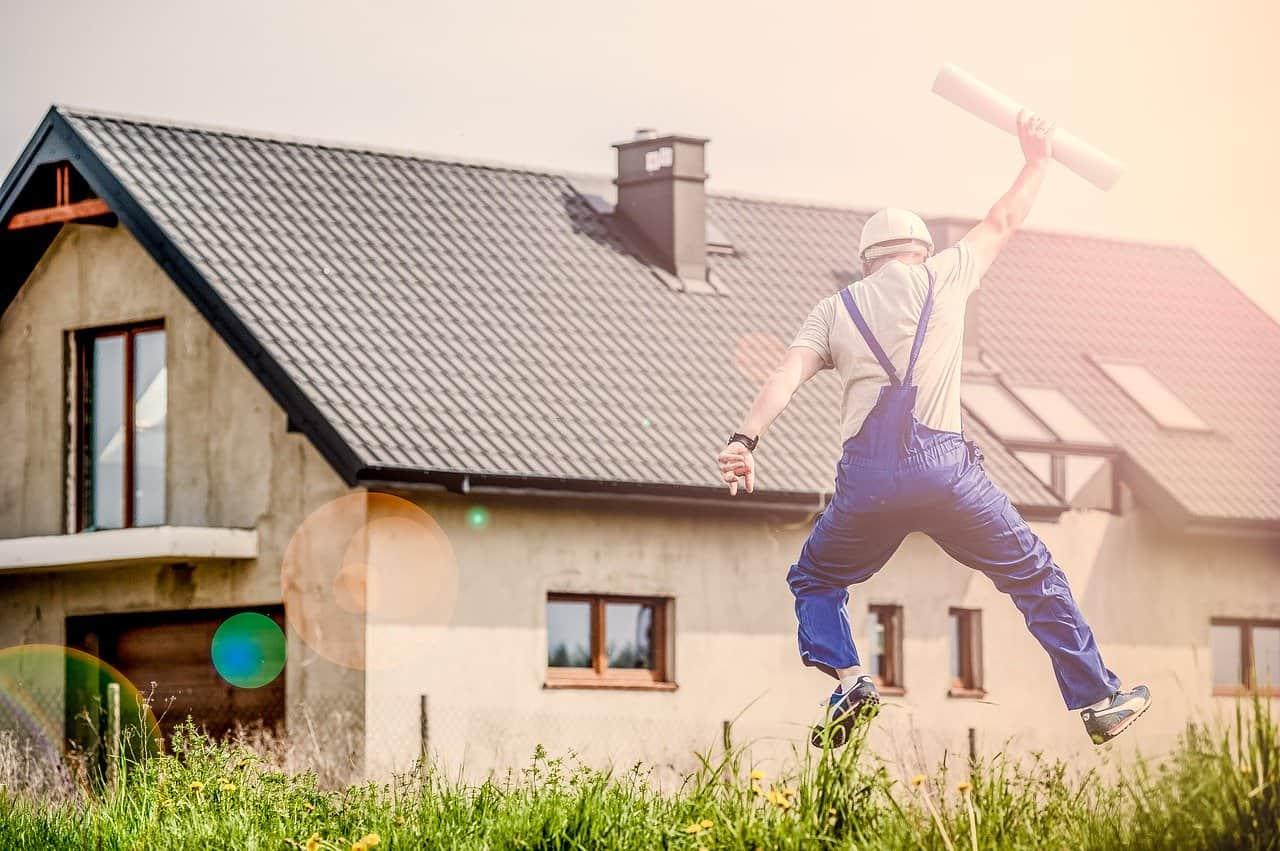 איש מקצוע עם קסדת בטיחות לבנייה קופץ בשמחה מול בית חדש